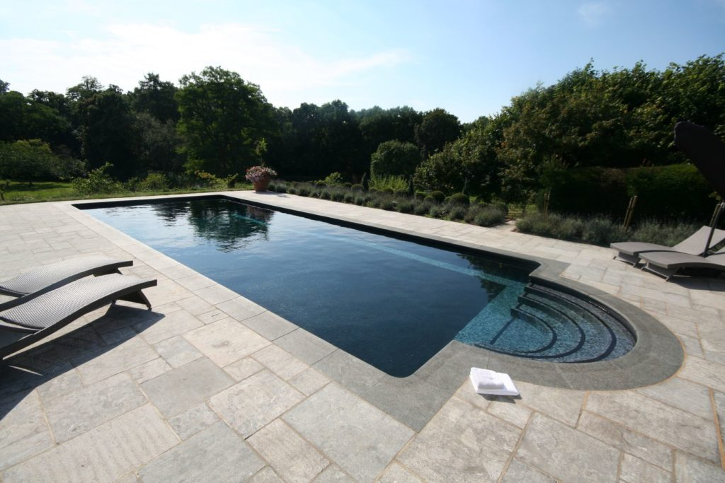 Classical Roman end pool in contemporary charcoal mosaic tiles with an automatic slatted cover