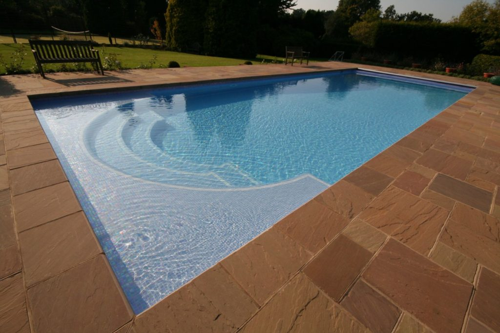 Classical Roman end pool with a twist to allow the installation of a safety cover with recycled iridescent mosaic tiles.