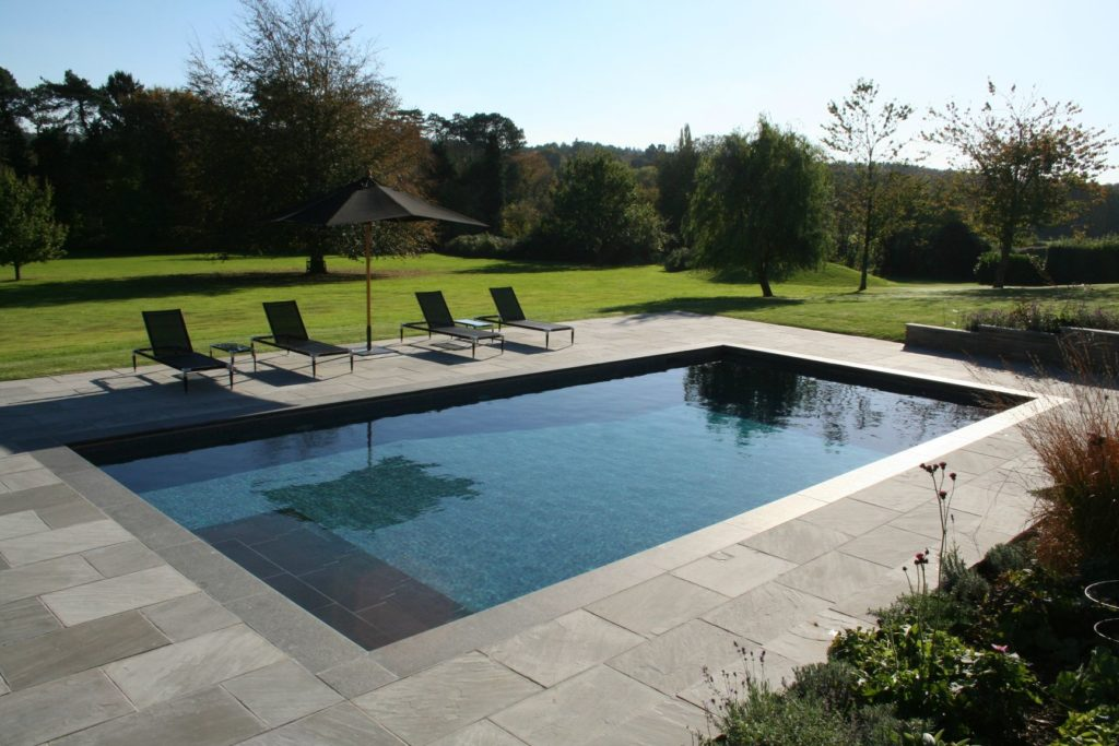 Country garden pool with charcoal mosaics, slate steps and copings