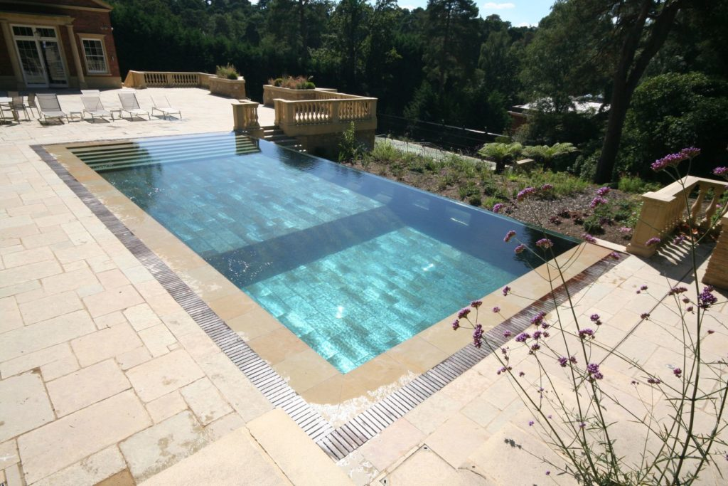 Infinity edge pool with wall windows and automatic slatted cover, full width steps and large format tiles