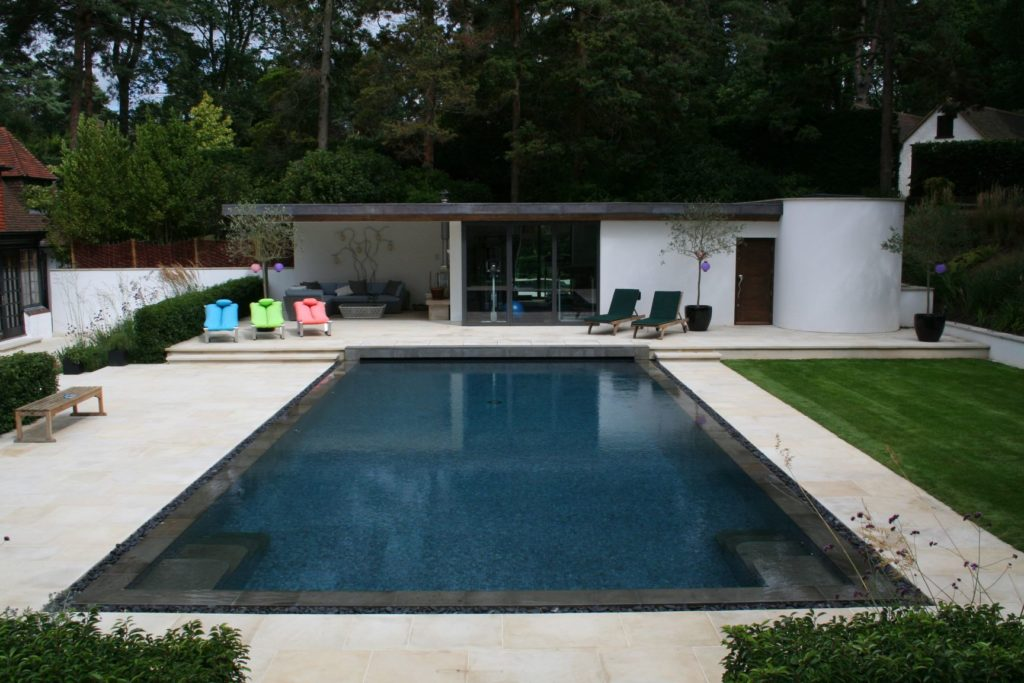 Decklevel outdoor pool with double steps and automatic slatted cover
